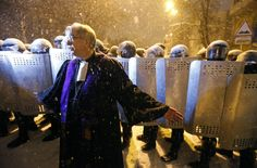 EuroMaidan; Kyiv, Ukraine 2013 A priest from the St. Elena Lutheran Church stands between protesters and police line.
