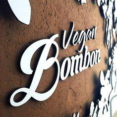Cardboard logo integrated into the sand at the vegan bakery Vegan Bombon. Sustainable decoration for interiors, retails and stores. Designed by Cartonlab. #BakeryDecor #ideastodecor #sustainabledecor