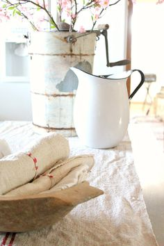 A stack of linen hand towels and rolled grainsack napkins sit in a round stoneware bowl...