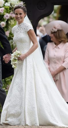 """May 20-17 Radiant Bride Pippa in a bespoke Giles Deacon creation: """"The dress is constructed with a cap sleeve, high neckline and features a corseted bodice with draping to the front and a heart-shaped detail at the back. The bespoke silk cotton lace was hand appliquéd to create the illusion of the dress having 'no seams'. The lace bodice is embroidered with pearl detailing over an organza and tulle underskirt, layer upon layer to enable a floor-sweeping movement."""""""