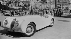 American actor Van Johnson, who became very popular during the war due to the absence of the established leading men, poses in his Jaguar XK120 parked in a crowded square