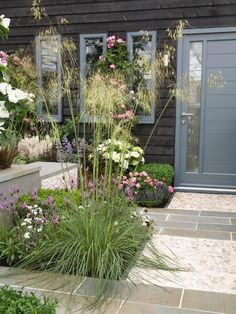 Slate and cobblestone play well together on this striking patio. Boxed plant beds provide a space to show off flowing grasses and a mix of pink, purple and white blooms.