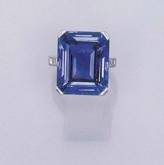 AN ATTRACTIVE SAPPHIRE RING, BY CARTIER   Set with a octagonal-cut sapphire weighing 29.06 carats to the square-cut diamond three-stone shoulders and plain hoop, with French assay mark  Signed Cartier, Paris, no. 69287