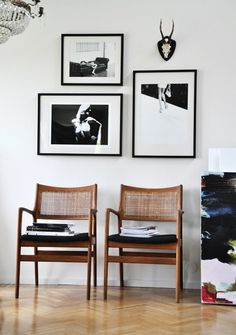 Three black and white photographs over chairs.