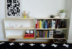 The shelves are comprised of two sets of steel EXBY OXIE brackets from IKEA and six EKBY TRYGGVE pine shelves.
