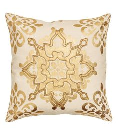 $25 Light beige/gold-colored. Cushion cover in cotton fabric with embroidery in metal thread and a shimmering, printed pattern at front. Solid-color back.