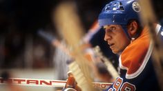 A fantastic shot of Wayne Gretzky on the bench deeply focused on the game, and the play.
