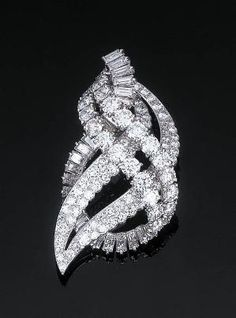 A Diamond Pendant Brooch by Cartier   Of scrolled openwork design, set with four circular-cut diamond rows with a further scrolled baguette-cut diamond line, hidden pendant hook, with French assay and maker's marks, in a fitted red leather case, 5.5 cm long  Signed Cartier, Paris, No. 012220 by hester