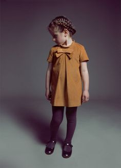 little girl dress. The eggplant tights are so cute on her! And I love the ultra short 1950s style hem. I'd make this with a little pair of matching shorts to be worn under.