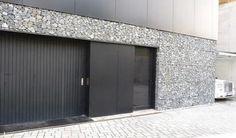 Thin gabion facade and dark doors