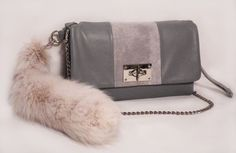 The Fashionjenn Handbag's Mimi Bag is handmade in delicious gray lambskin. It has polished nickel hardware with a removable chain strap, wristlet strap and fox tail accent. A classic front flap bag perfect for day or night!