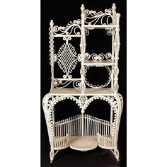ETAGERE. Victorian white wicker etagere having ornate, scrolling decorative elements throughout, with four stepped tiers and scalloped lower tier, rising on splayed openwork feet