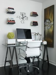 Chic modern office with glass-top sawhorse desk, Eames Management Chair- White, abstract canvas art and floating bookshelves.
