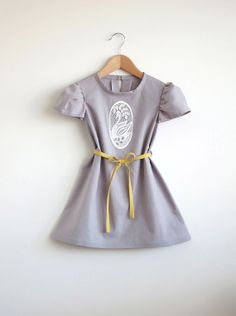 Made from 100% cotton in a pretty pearl gray, this short sleeved dress is adorned in front with a vintage lace swan appliqué. Loops at waist...