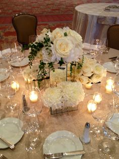 Mirror vases with white flowers and votive candles