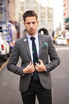 Grey flannel blazer, blue oxford shirt, grey lapel flower. green and white polka dot pocket square, Green navy and black tartan tie, black woolen pants