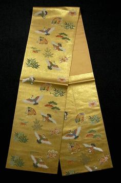 This is a graceful Fukuro obi with auspicious design of fan, crane and 'Shou-chiku-bai'( pine tree, bamboo and ume blossom), which is woven on the tranquil gold background