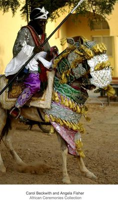 Africa | A mounted royal cavalier stands guard outside the palace of the Emir of Katsina. Thier regalia is reminiscent of earlier forms of protective covering worn for battle by their warrior ancestors. Hausa, Katsina, Nigeria. | ©Carol Beckwith and Angela Fisher