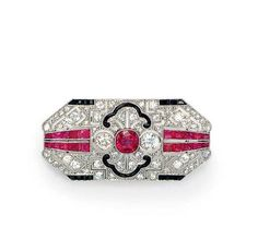 AN ART DECO DIAMOND, RUBY AND ONYX BROOCH   Designed as a pierced old European and rose-cut diamond rectangular tapered plaque, bezel-set with a central cushion-cut ruby, flanked on either side by a bezel-set old mine or old European-cut diamond, with French-cut ruby and black onyx, and black enamel geometric detail, mounted in platinum, circa 1925
