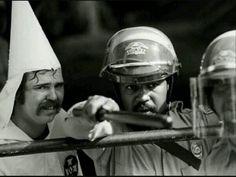 18 prachtige foto's van de mens en zijn roerige geschiedenis — Een zwarte agent beschermt iemand van de KKK tegen demonstranten (1983)