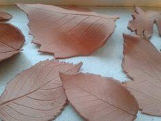 Bladeren van klei! Rol een dunne laag boetseerklei uit met behulp van een deegroller,  druk daarop een mooi herfstblad, snij de vorm uit, verwijder het herfstblad en zie hier het resultaat!