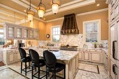 Neoclassical kitchen. warm neutral colored wall paint, marble tiled flooring, marble counter tops and back splash.