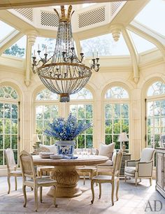 A bright conservatory that also serves as a breakfast room features an Italian marble pedestal table | archdigest.com