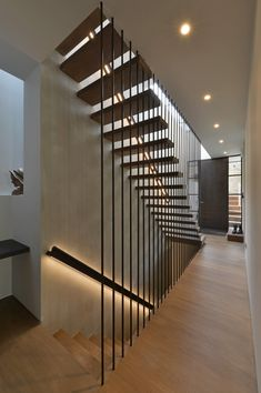 These modern wood stairs have a handrail with hidden lighting, and a floor-to-ceiling steel rod safety barrier. Wood Stair Handrail, Wall Mounted Handrail, Wood Stairs, House Stairs, Railings, Home Stairs Design, Interior Stairs, Modern House Design, Modern Stairs Design
