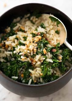 Garlic Butter Rice with Kale in a dark brown bowl with a silver spoon, ready to be eaten.