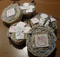 Decori per l'albero in cartone: questa è un'idea che mi ha dato un'amica. Ho utilizzato uno scatolone del latte e del cartoncino leggero, come quello dei cereali. Ho tagliato a strisce il cartone e incollato, arrotolato su se stesso. Nella parte più esterna della striscia ho praticato un foro dal quale ho fatto passare un anellino di lana. Ho tagliato dei quadratini di cartoncino e li ho timbrati, poi incollati sulle palline.