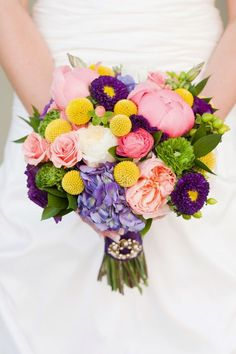 A cheery, multicolor bouquet featuring shades of light coral, yellow, lavender, green, and purple.