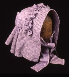 1900 - 1925 Mauve canal bonnet made from printed cotton with decorative ruffle across the crown and corded quilting along the brim. The bonnet has two ties made from the same fabric. Used on the Kennet and Avon Canal