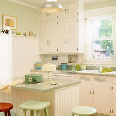 Mellow Yellow  Painting old cabinets crisp white (plus polishing existing hardware) saves them for another decade of use. Repeating the beaded-board backsplash on a new island gives everything the same old-time flavor.