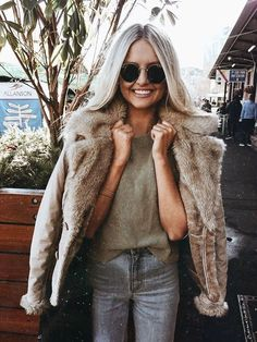 Faux fur jacket over olive tee and blue jeans.