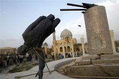 A statue of Saddam Hussein falls in central Baghdad on April 9, 2003. Iraqis earlier took a sledgehammer to the marble plinth under the statue. Youths had placed a noose around the statue's neck and attached the rope to a U.S. armored vehicle to pull it down