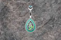Purple opal belly button rings. Purple synthetic opal belly ring. This synthetic opal has flecks of blues and greens and is the shape of a teardrop, with a teal enameled decorative edging. Opal settin