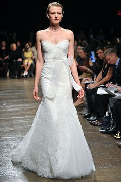 Monique Lhuillier... Lace gown features a tulle underlay and self-tied horsehair bow at natural waist.