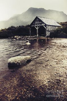 Vintage style landscape of an old watershed or shack by a foggy winter lake. Taken at the historical Boat Shed on Dove Lake Cradle Mountain, Tasmania, Australia by Ryan Jorgensen