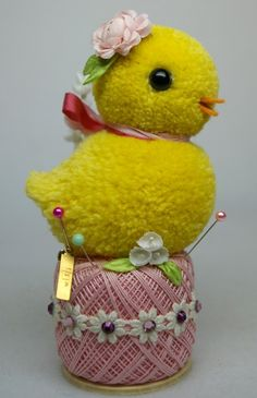 A cute little Easter chick sits on a spool of pink thread that has been embellished with white trim, millinery flowers and crystals. It doubles