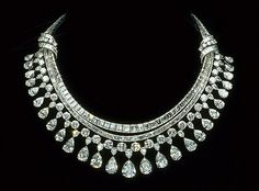 "The 'Hazen Diamond Necklace' designed by Harry Winston contains 325 diamonds that have a total weight of approximately 131.43 carats set in platinum. The necklace has two sections: the upper section is a single row of emerald cut diamonds, and the lower section consists of 3-rows - a row of baguette cut diamonds and a row of round brilliant cut diamonds from which a ""fringe"" of pear-shaped diamonds are suspended."