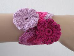 Deze mooie cuff armband is gehaakt in diverse tinten roze katoen in een chevron- of golfpatroon. De bloemen op de armband zijn van dezelfde tinten gemaakt.