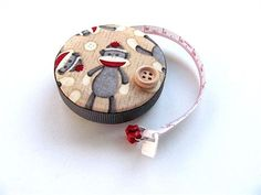 Classic sock monkeys cover both sides of this retractable tape measure. The tape is encircled with a gray ribbon and a coordinating button is an embellishment on the top. A red, bead charm is attached to the tapes pull tab.   The retract button is on the back. The tape measures 2 (5cm)across  measures to 60 and 150cm.   I carry a tape measure everywhere! It comes in so handy. Keep it in your purse for shopping and crafts on the go.   For knitters and sewers this makes a delightful gift…