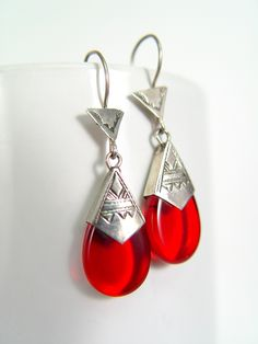 """Silver and Red Glass Toureg Earrings   Handmade.  The Tuareg are a nomadic tribe in the North African Sahara often associated with the Berbers. Their jewelry is unique and highly prized, and they're best known for their engraved silver jewelry. These beautifully handmade earrings feature a red glass pendant and etched silver.  92.5% pure silver.  Length of Earrings: 1 2/3""""  Made in: Mali.  $30.00"""