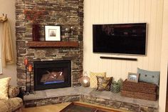 A cozy stone veneer gas fireplace with shiplap wall and flat screen television.