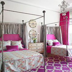 A bold patterned area rug forms the foundation for this stylish bedroom for two. The striking fuchsia hue of the rug makes its way onto other elements throughout the room, such as the headboards and bedding. A foundation of gray on the walls, bedding, and accents helps temper and refine the wild color.