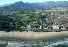 Strand North suburb and the Strand Golf Club visible behind the entrance to Strand  Beach Road's first few apartment blocks on Melkbaai. Helderberg mountain on the left and the Hottentots-Holland mountain range lies to right. #strand #beachroad #strandnorth #strandgolfclub #golfclub
