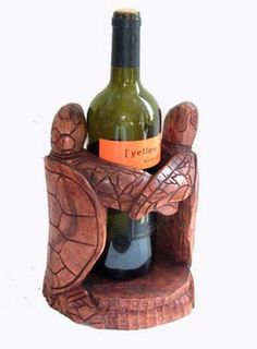 Two turtles join to create this unique wine holder. Hand carved out of one piece of wood by skilled carvers.    Origin: Indonesia