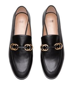 Black. Loafers with a decorative seam and metal rings at front. Faux leather lining and insoles. Rubber soles. Heel height 1/2 in.