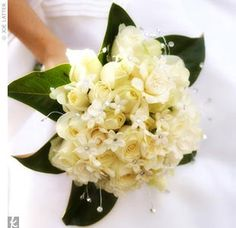 FAVORITE! all-white bouquet of roses, gardenias, and stephanotis with a magnolia leaf collar. The stephanotis were seeded with crystals, while crystals were also mixed in with the blooms and in the white satin wrapped around the stems -- LOVE but no crystals, add pearls with fuller roses and bigger and fuller