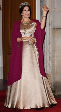 Simply elegant: Crown Princess Mary of Denmark waved on the red carpet, a matching gold clutch held in her right hand